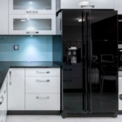 Kitchen with black fridge, white cabinets and black countertops.