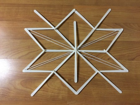Stick and Yarn Snowflake Decoration - glue yarn down to center on each pass