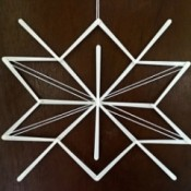 Stick and Yarn Snowflake Decoration - finished snowflake hanging on the wall