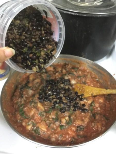 adding black beans to skillet