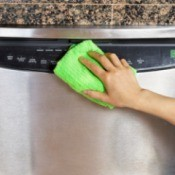 Hand wiping down a stainless steel dishwasher.