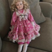 Identifying an Antique Porcelain Doll - blond doll with ringlets and wearing a pink and white floral dress