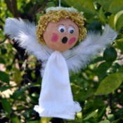 Lace Frill Sock Christmas Angel - finished angel with wings added hanging from a tree branch