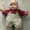 Identifying a Porcelain Doll - doll wearing a red print shirt and overalls