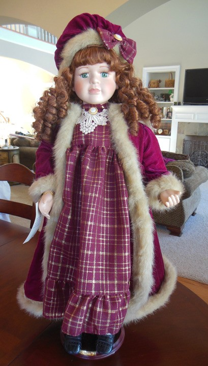 Value of a Collectible Memories Porcelain Doll - red haired doll wearing a red coat with fur trim and a plaid dress