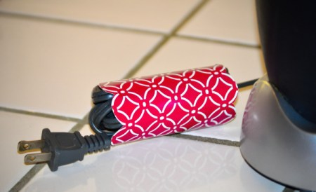 A piece of recycled cardboard from a tissue box, wrapped around an appliance cord.