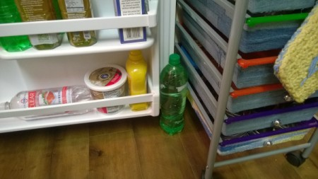 A bottle of soda holding a refrigerator door open.