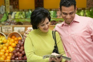 Woman and Man Looking at Coupons in Supermarket