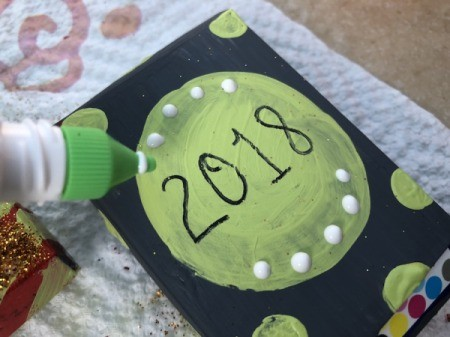 Snack Box New Year's Noisemakers - adding glue dots and sprinkle with glitter