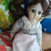 Identifying a Porcelain Doll - doll wearing a floral dress and apron