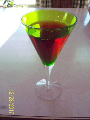 A green glass filled with a red liquid.