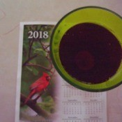 A green glass filled with a red liquid on top of a 2018 calendar.