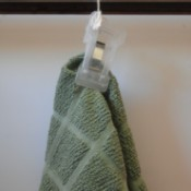 A kitchen towel hung on a oven handle by using a clip.