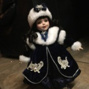 Identifying a Porcelain Doll - dark haired doll wearing a fur trimmed coat and fur hat