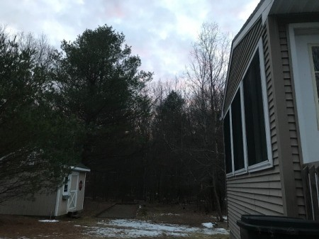 Snow on the ground near a house.