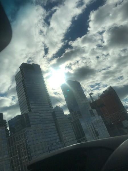 The sun peeking through tall buildings in winter.