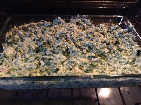 A baking dish filled with spinach artichoke dip.