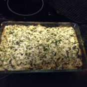 A baked dish of spinach artichoke dip.
