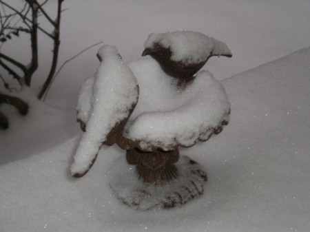 A garden sculpture of two birds covered in snow.