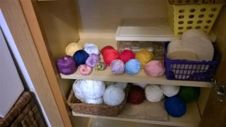 Skeins of yarn on a shelf.