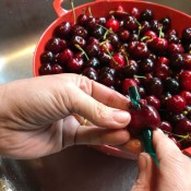 A straw being pushed through a whole cherry, to remove the pit.