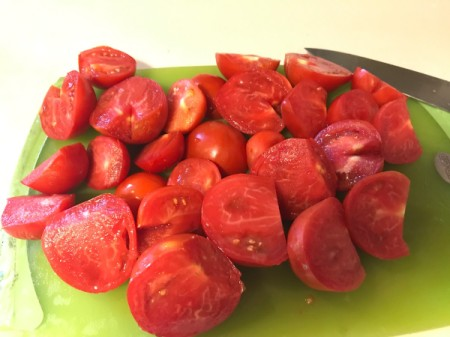 A cutting board full of tomatoes that have been cut into quarters.