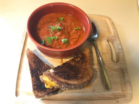 A bowl of Roasted Tomato Soup with a grilled cheese sandwich.