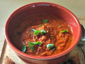 A bowl of Roasted Tomato Soup with basil as a garnish.