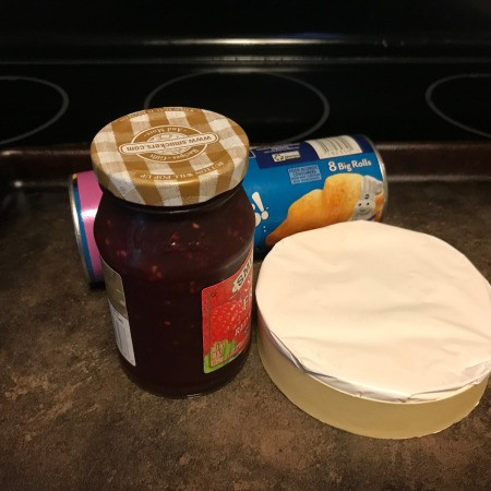 A jar of jam, a package of refrigerator crescent rolls and a package of brie.