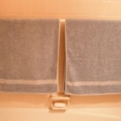 A shower rod in the bathtub used for hanging towels.