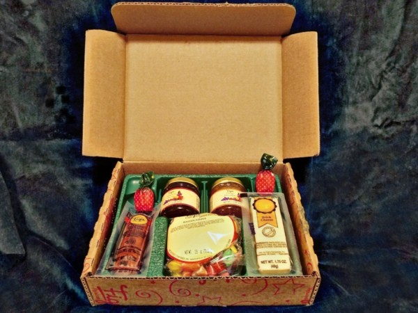 A Christmas box with a selection of summer sausage, cheese and jams.