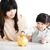 Woman Showing Daughter how to Save Money with Piggy Bank