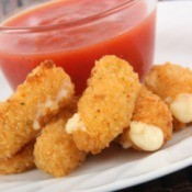 A plate of fried breaded cheese sticks with tomato sauce.