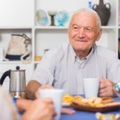 Elderly Man Sitting at Table Eating