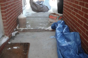 A tarp on the ground outside to protect the concrete from ice and snow.