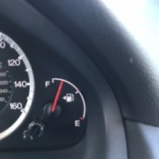 The fuel tank indicator in a car, with the arrow pointing to the side with the gas cap.