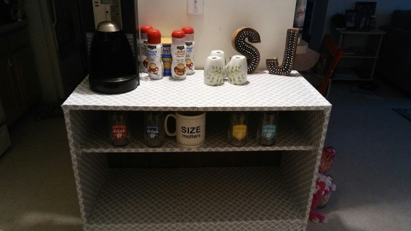 A white shelf with a coffee center and some condiments.