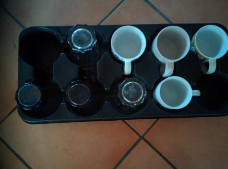 A plant tray being reused for coffee mugs and glassware.