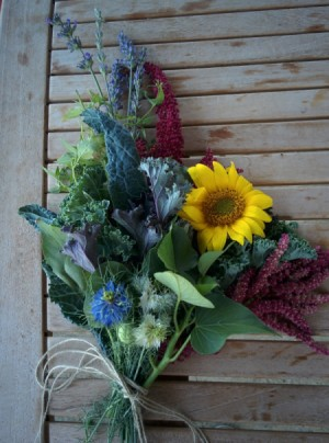 A bouquet of edible flowers on a wooden table.