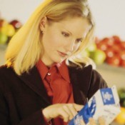Woman Looking at Expiration Date on Carton