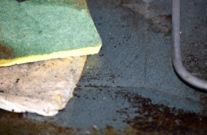 A dirty oven with wet paper towels and a scrubby sponge.