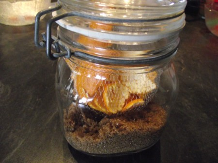 Orange peels inside a jar of brown sugar.