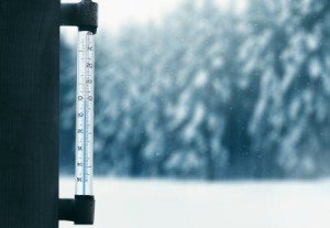 A thermometer with snowy weather outside.
