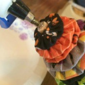 Glue being applied to the end of a Halloween Yo Yo Tree.
