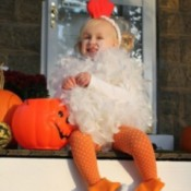 A toddler in a fluffy chicken costume for Halloween.