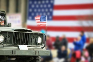 Close up of a Jeep with American flag flying on the hood and an American flag in the background.
