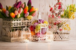 White wire birdcages filled with easter eggs and tulips.