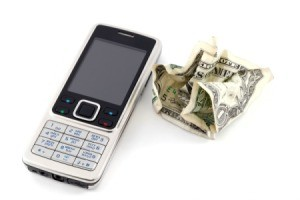 Cellphone next to a crumpled dollar bill.