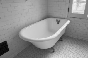 Cast Iron Tub in a white tiled bathroom.