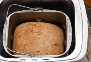 Closeup of cooked loaf of bread in a bread machine.